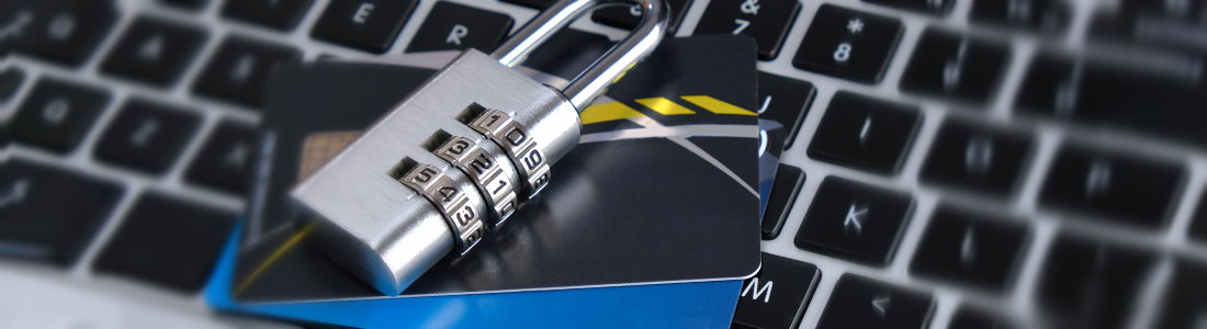 a padlock on top of credit cards that are on a keyboard