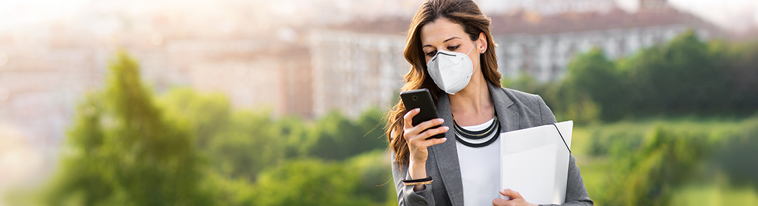 A woman using a mobile device running errands outside wearing a mask