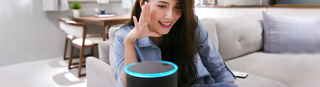 A woman talking into her smart speaker