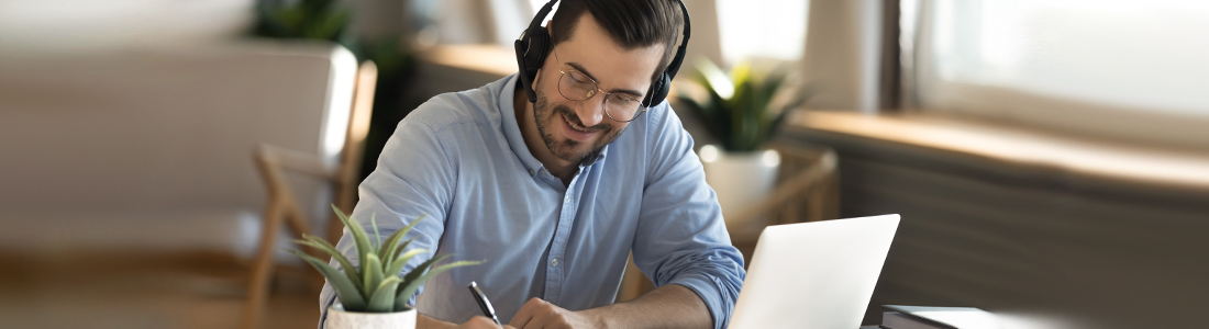 a man wearing a headset on a laptop while writing on a paper